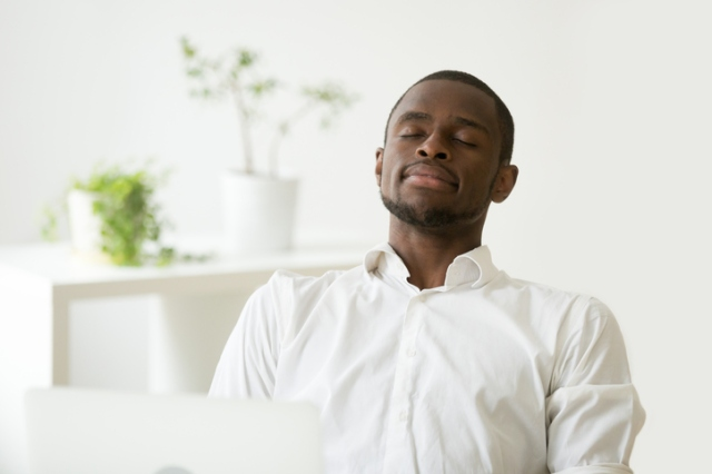 Satisfied African American worker meditating at workplace managi